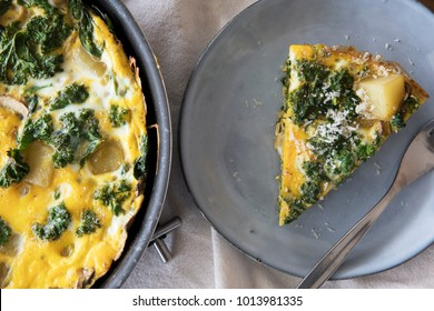 Delicious frittata with kale and potatoes in pan and slice on plate