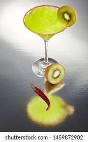 Delicious frozen kiwi Margarita cocktail rimmed with salt and bird's beak chili pepper and a slice of kiwi on a reflective surface with a full dry chili pepper.