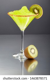 Delicious frozen kiwi Margarita cocktail rimmed with salt and bird's beak chili pepper and a slice of kiwi with a great reflection.