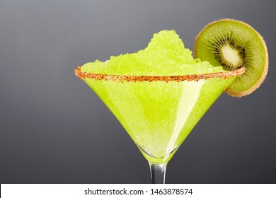 Delicious frozen kiwi Margarita cocktail rimmed with salt and bird's beak chili pepper and a slice of kiwi with a great reflection. Close up.