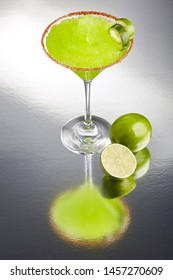 Delicious frozen lime Margarita cocktail rimmed with salt and bird's beak chile or pepper and a twist of lime by a lime and a slice of lime on a grey background with a great reflection.