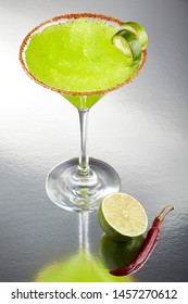 Delicious frozen lime Margarita cocktail rimmed with salt and bird's beak chile or pepper and a twist of lime by a slice of lime and a full dry bird's beak chile, on a grey background