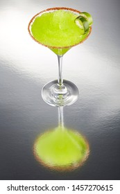 Delicious frozen lime Margarita cocktail rimmed with salt and bird's beak chile or pepper and a twist of lime