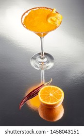 Delicious frozen orange Margarita cocktail rimmed with salt and bird's beak chili pepper and a twist of orange on a silver table with an amazing reflection
