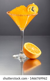 Delicious frozen orange Margarita cocktail rimmed with salt and bird's beak chili pepper and a twist of orange, by half an orange on a grey background.