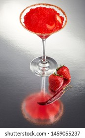 Delicious frozen strawberry Margarita cocktail rimmed with salt and bird's beak chili pepper and a twist of strawberry on a silver table with two full fruits and a full dry chili pepper