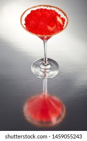 Delicious frozen strawberry Margarita cocktail rimmed with salt and bird's beak chili pepper and a twist of strawberry on a silver table with an amazing reflection