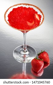 Delicious frozen strawberry Margarita cocktail rimmed with salt and bird's beak chili pepper and a twist of strawberry on a silver table with two full fruits and a great reflection