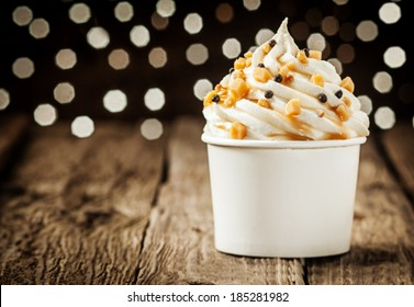 Delicious frozen yogurt party dessert twirled in a tub and decorated with sprinkles against a sparkling bokeh of festive lights