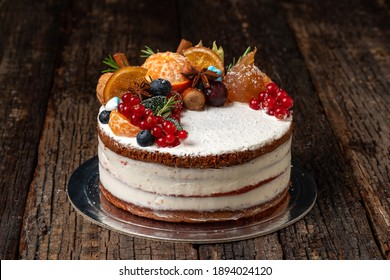Delicious fruit cake made from delicious ingredients and cream, on a wooden textured background. Close-up.