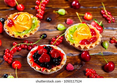 Delicious fruit cake on brown wooden background with strawberries, cherries, currants and raspberries. Beautiful, delightful and healthy desserts