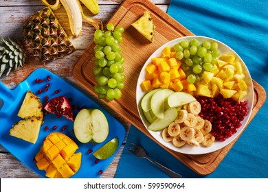 delicious fruit salad with banana and green apple slices, chunks of mango and pineapple, grapes, seeds of the garnet laid out on segments on platter on chopping board, view from above