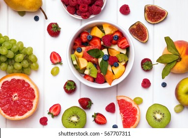 Delicious fruit salad and different fruits and berries on the white table, top view