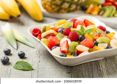 Delicious fruit salad with fresh fruit. Wooden, gray table in the background. Front view.
