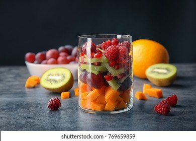 Delicious fruit salad in jar on table