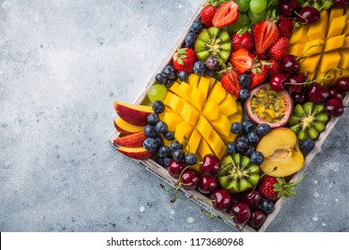 delicious fruits and berries platter.  Mango, kiwi, strawberry, grape, cherry, blueberry, peach and passion fruit, top view, copy space