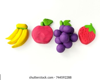 Delicious fruits made from clay plasticine (banana,apple,grapes,strawberry) are placed on white background,colorful cute dough