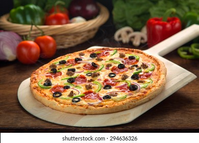 Delicious full supreme deluxe pizza baked fresh out of the oven next to ingredients