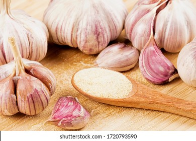 Delicious Garlic bulbs and cloves with a spoon of garlic powder on a wooden cutting board