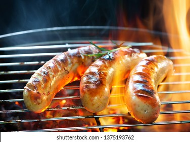 Delicious german sausages sizzling over the coals on barbecue grill