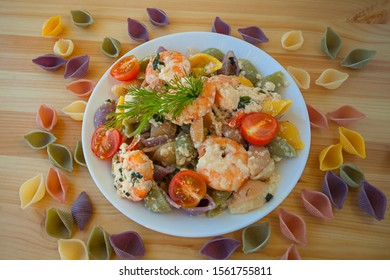 delicious gigli t with shrimps and basil on a plate on a wooden background