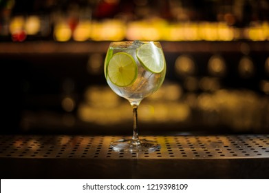 Delicious Gin Tonic cocktail decorated with lime slices standing on the steel bar counter on the blurred background