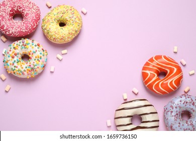 Delicious glazed donuts on lilac background, flat lay. Space for text