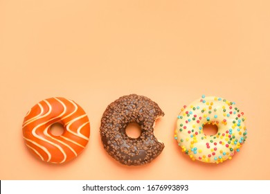 Delicious glazed donuts on orange background, flat lay. Space for text
