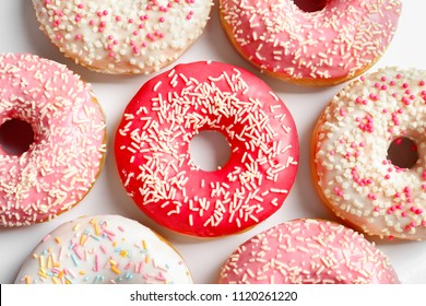 Delicious glazed doughnuts with sprinkles on light background, top view
