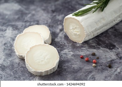 Delicious goat cheese slices and piece with fresh rosemary leaves on stone  background. Luxurious culinary cheese still life.