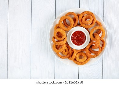 delicious golden battered, breaded and deep fried crispy onion rings served on white platter with ketchup in center, view from above