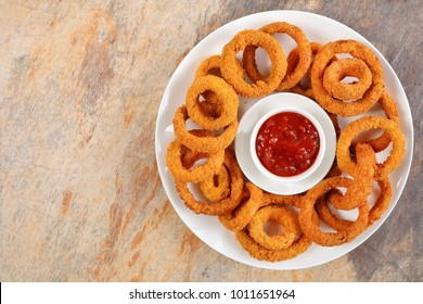 delicious golden battered, breaded and deep fried crispy onion rings with ketchup in center on white platter on stone tray, view from above