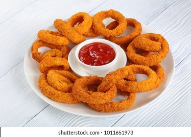 delicious golden battered, breaded and deep fried crispy onion rings served on white platter with tomato  sauce in center, side view from above, close-up