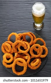delicious golden battered, breaded and deep fried crispy onion rings served on round black stone tray on black wooden table with glass of foamed beer at background, vertical view from above
