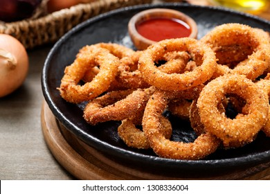Delicious golden battered, breaded and deep fried crispy onion rings with ketchup.