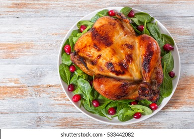 delicious golden crispy skin whole chicken grilled in oven and arugula, spinach and cranberry salad on white plate on old white peeling paint boards, view from above, copy space left