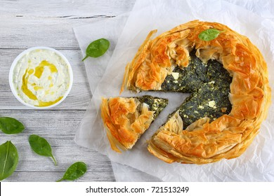 delicious golden crust hot greek spinach feta cheese pie or spanakopita cut in slices on white paper with tzatziki sauce in bowl on old table, authentic recipe, view from above