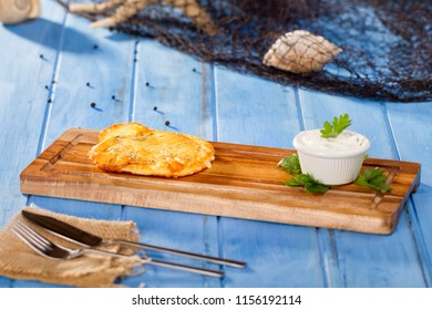 Delicious Golden Fried Jumbo Greek Saganaki Cheese at bamboo plate serving with fishing net, shell, knife, fork and napkin on rustic blue wood table background. Copy space for text area.