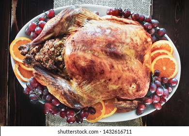 Delicious golden roasted and stuffed Thanksgiving Day turkey  on a platter garnished with fresh grapes and parsley over a rustic farmhouse table background.