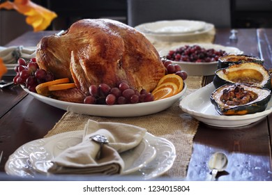 Delicious golden roasted Thanksgiving turkey  on a platter garnished with fresh grapes and slices of oranges on a rustic farmhouse table.
