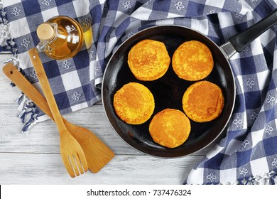 delicious golden yellow pumpkin pancakes on skillet on wooden table with kitchen towel, wooden spatulas and bottle of olive oil, view from above