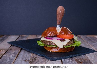 Delicious gourmet cheeseburger with knife on dark wooden background