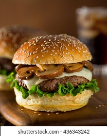 A delicious gourmet hamburger topped with swiss cheese and fried mushrooms on a rosemary sesame seed bun.