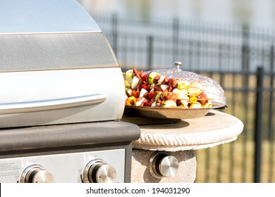 Delicious gourmet kebabs ready to be barbecued standing on a metal plate in the summer sunshine alongside a closed gas BBQ