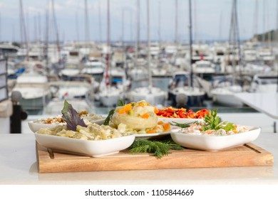 Delicious Greek and Turkish Olive Oil Flavored Mix Appetizer Plate with Artichoke Heart Stuffed with Carrot, Green Pea and Fresh Yogurt. Luxury yacht marine and sea background, copy space for text.