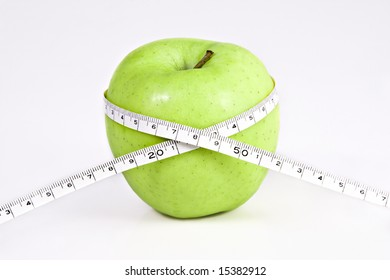 delicious green apple on white background with a  measuring tape around it.