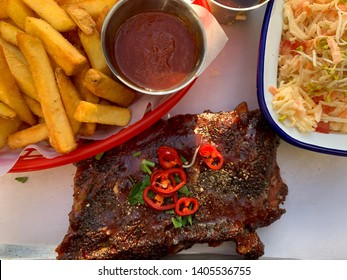 Delicious grill spareribs with black pepper, herbs and chili pepper close up, traditional American spare ribs spices, french fries and cole slaw on the plate close up