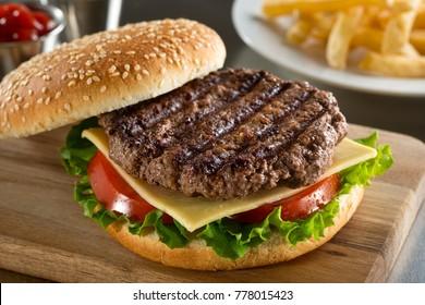 Um delicioso hambúrguer Angus grelhado com queijo, alface e tomate em um pão de gergelim.