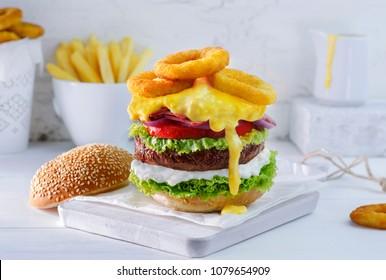 Delicious grilled beef burger with layers of lettuce, mayonnaise,tomato,onion, bacon, melted cheddar cheese and fried onion rings. Served with french fries and cheese sauce.