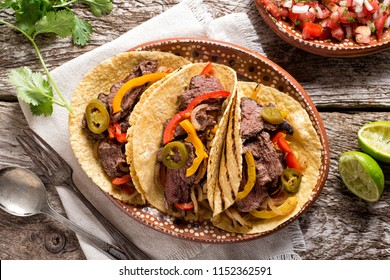 Delicious grilled beef fajitas with steak, onion, bell peppers and jalapeno.